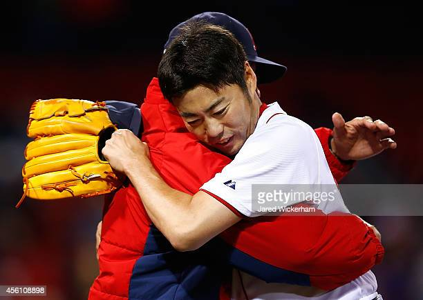 Koji Uehara of the Boston Red Sox hugs pitching coach Juan Nieves following his save in the 9th inning against the Tampa Bay Rays during the game at...