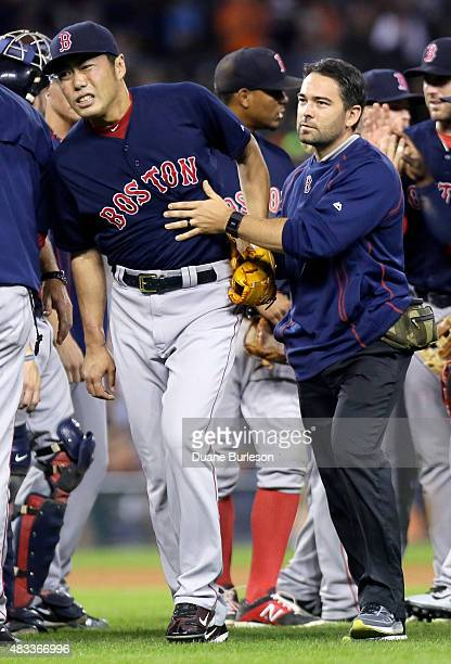 Koji Uehara of the Boston Red Sox is led off the field by trainer Brad Pearson after taking a line drive off the right wrist from Ian Kinsler of the...
