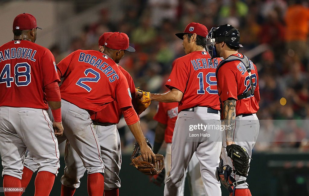 Koji Uehara #19 of the Boston Red Sox leaves the game in the fifth inning and is congratulated by his teammates during the Spring Training Game on March 16, 2016 at CenturyLink Sports Complex and Hammond Stadium, Fort Myers, Florida.