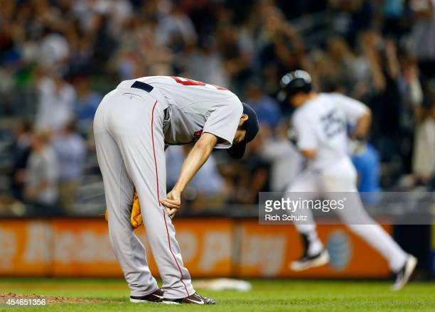 Koji Uehara of the Boston Red Sox reacts after giving up a game tying homerun to Mark Teixeira of the New York Yankees who round first base during...