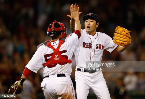 Koji Uehara of the Boston Red Sox reacts with Christian Vazquez after the final out against the Kansas City Royals to give the Red Sox a 21 win at...