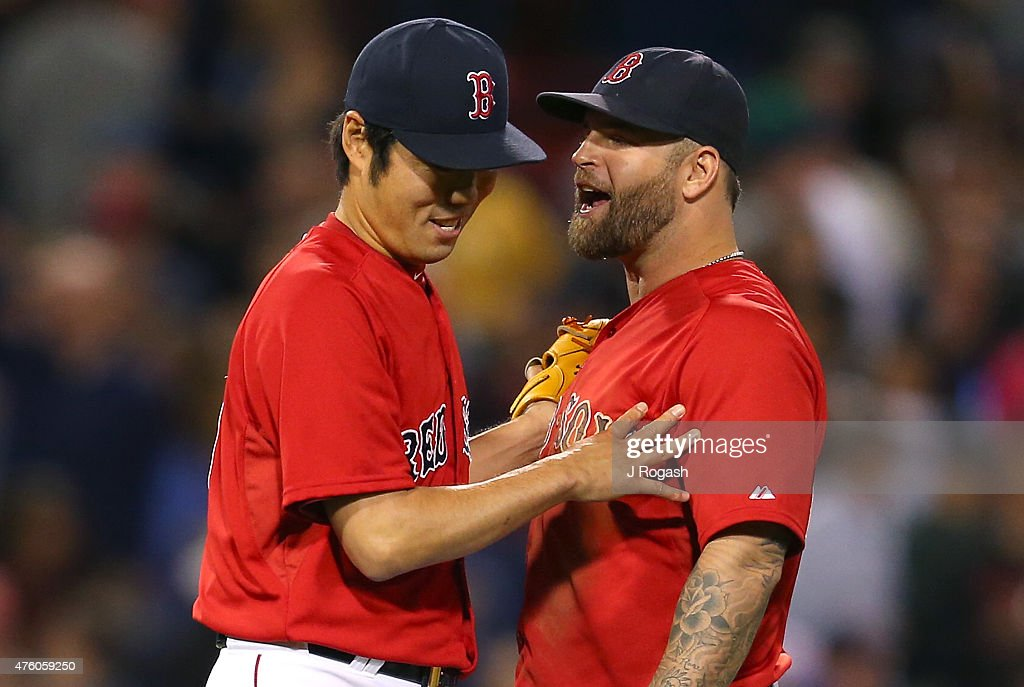 Koji Uehara #19 of the Boston Red Sox reacts with Mike Napoli #12 of the Boston Red Sox after a win against Oakland Athletics at Fenway Park on June 5, 2015 in Boston, Massachusetts.