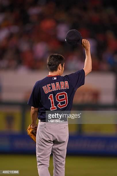 Koji Uehara of the Boston Red Sox tips his cap to teammate center fielder Jackie Bradley Jr #25 during the game against the Los Angeles Angels of...