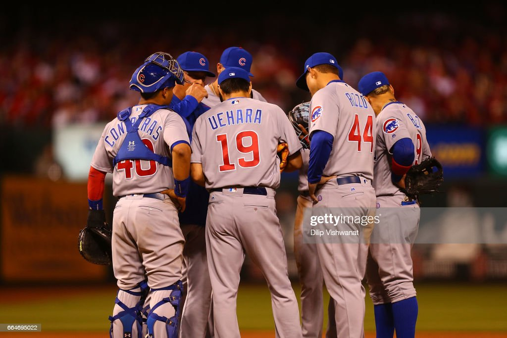 Koji Uehara #19 of the Chicago Cubs meets with teammates against the St. Louis Cardinals in the seventh inning at Busch Stadium on April 3, 2017 in St. Louis, Missouri.