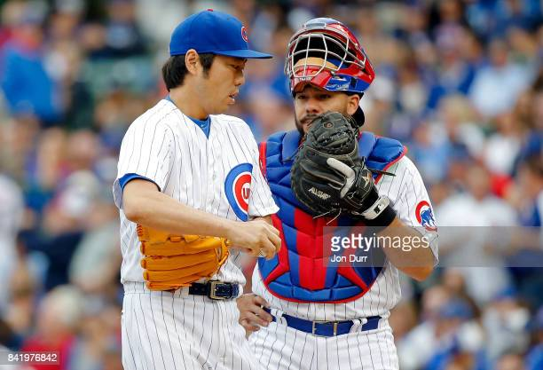 Koji Uehara of the Chicago Cubs talks with Rene Rivera during the seventh inning of their game against the Atlanta Braves at Wrigley Field on...