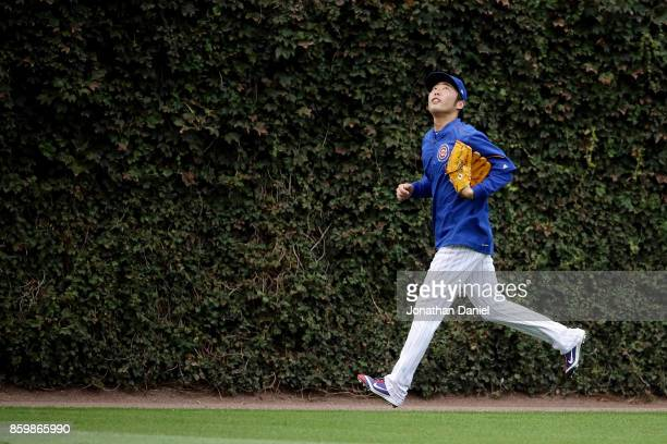 Koji Uehara of the Chicago Cubs warms up before game four of the National League Division Series against the Washington Nationals at Wrigley Field on...