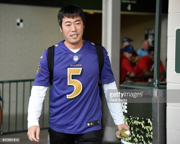 Koji Uehara of the Chicago Cubs wears a football jersey as the Cubs leave on their road trip on September 3 2017 at Wrigley Field in Chicago Illinois