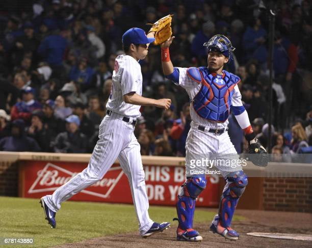 Koji Uehara of the Chicago Cubsis greeted by Willson Contreras of the Chicago Cubs after getting the third out against the Philadelphia Phillies...