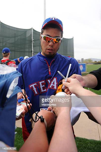 Koji Uehara of the Texas Ranges signs autographs for fans during a workout session at the Surprise Sports Complex on March 5 2012 in Surprise Arizona