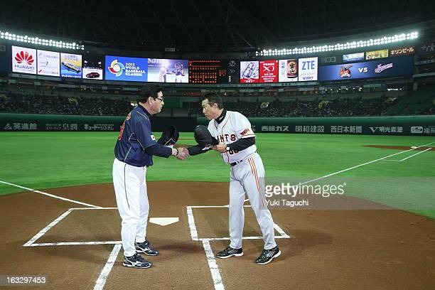 Koji Yamamoto manager of Team Japan shakes hands with Tatsunori Hara manager of the Yomiuri Giants before the 2013 World Baseball Classic exhibition...