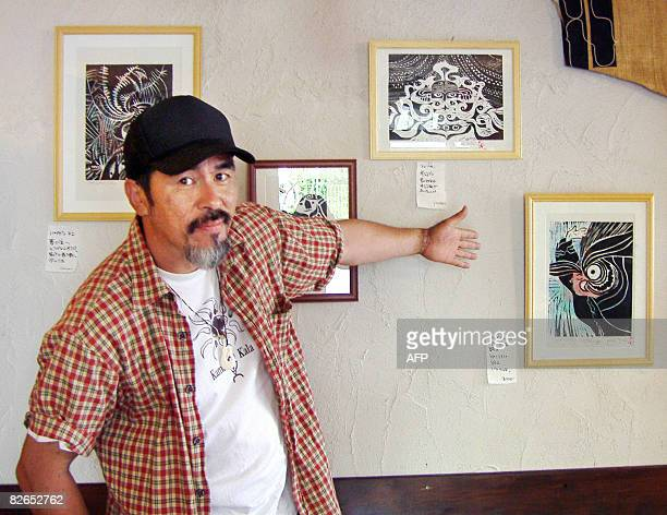 Koji Yuki indigenous Ainu and woodblock artist shows his woodblock prints during his personal exhibition at a cafe in Sapporo in Japan's northern...