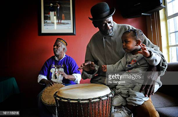 Kojo John Marsh left with Ralph Mills center teaches his grandson Destine Mills to play the West African drums during a celebration for the first day...
