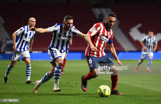 Koke of Atletico de Madrid battles for possession with Joseba Zaldua of Real Sociedad during the La Liga Santander match between Atletico de Madrid...