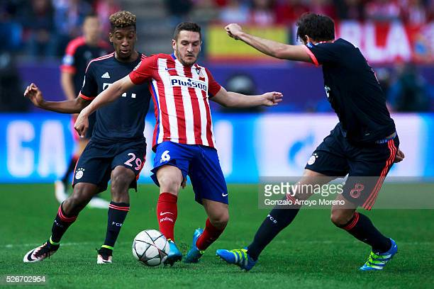 Koke of Atletico de Madrid competes for the ball with Kingsley Coman and Javi Martinez of Bayern Munich during the UEFA Champions League Semi Final...