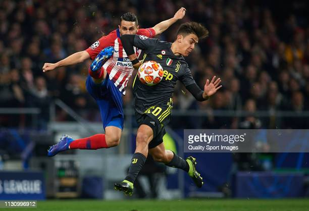 Koke of Atletico de Madrid competes for the ball with Paulo Dybala of Juventus during the UEFA Champions League Round of 16 First Leg match between...
