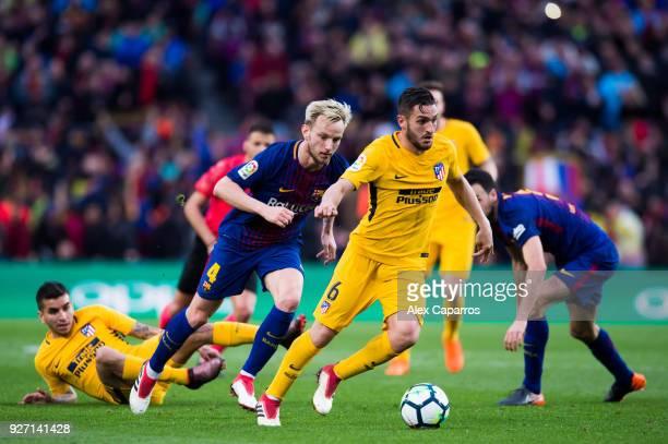 Koke of Atletico de Madrid conducts the ball under pressure from Ivan Rakitic of FC Barcelona during the La Liga match between Barcelona and Atletico...