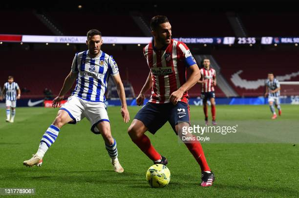 Koke of Atletico de Madrid is challenged by Aritz Elustondo of Real Sociedad during the La Liga Santander match between Atletico de Madrid and Real...