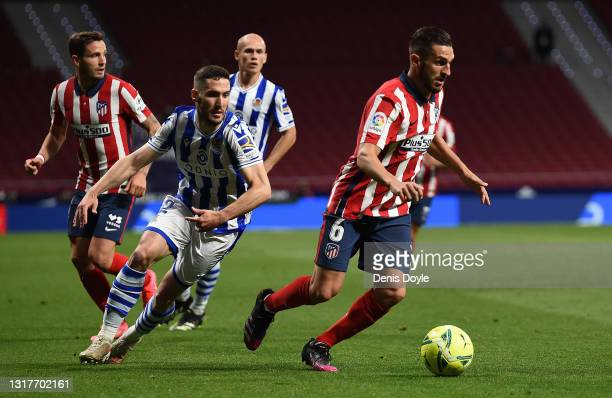 Koke of Atletico de Madrid is challenged by Joseba Zaldua of Real Sociedad during the La Liga Santander match between Atletico de Madrid and Real...