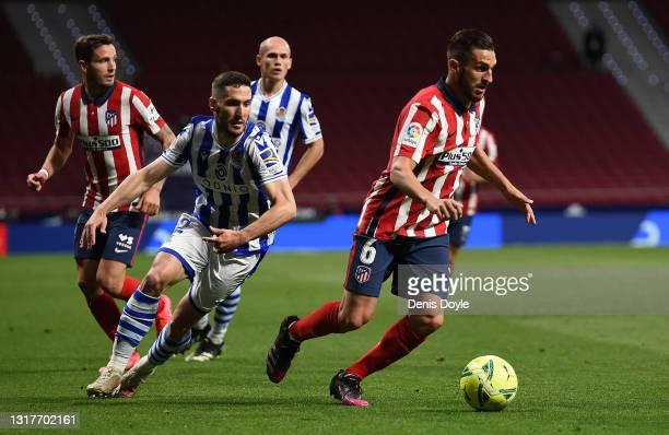 Koke of Atletico de Madrid is challenged by Joseba Zaldua of Real Sociedad during the La Liga Santander match between Atletico de Madrid and Real...