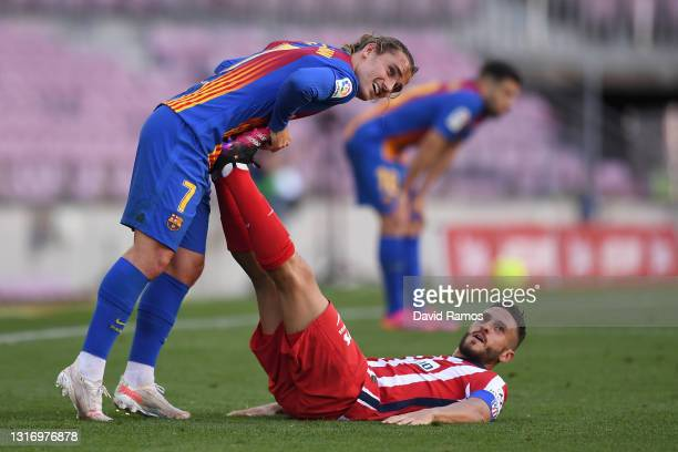 Koke of Atletico de Madrid receives treatment for cramp from Antoine Griezmann of FC Barcelona during the La Liga Santander match between FC...