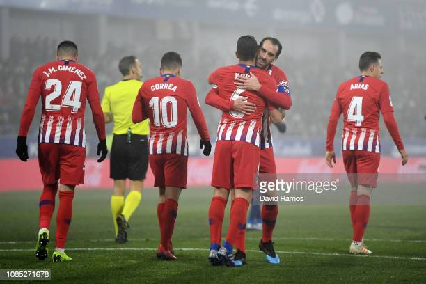 Koke of Atletico Madrid celebrates with teammate Diego Godin after scoring his team's third goal during the La Liga match between SD Huesca and Club...