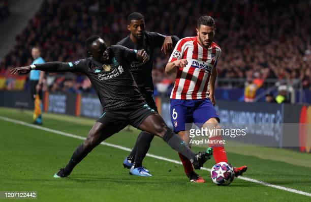Koke of Atletico Madrid is challenged by Georginio Wijnaldum and Sadio Mane of Liverpool during the UEFA Champions League round of 16 first leg match...