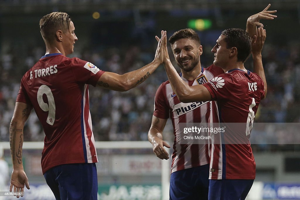 Koke #6 of Atletico Madrid is congratulated by team mates Fernando Torres #9 and Guilherme Siqueira #3 after scoring a goal from a corner kick against Sagan Tosu F.C. during the friendly match between Atletico Madrid and Sagan Tosu F.C. at Tosu Stadium on August 1, 2015 in Tosu, Japan.