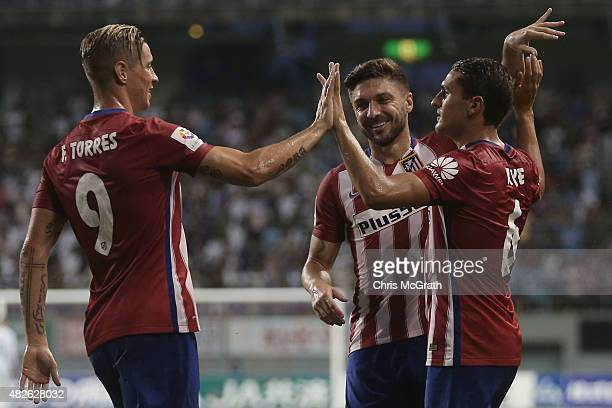 Koke of Atletico Madrid is congratulated by team mates Fernando Torres and Guilherme Siqueira after scoring a goal from a corner kick against Sagan...