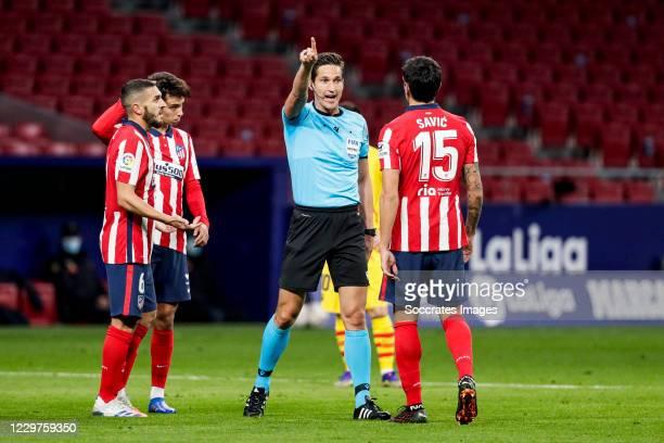 Koke of Atletico Madrid Joao Felix of Atletico Madrid referee Jose Luis Munuera Montero Stefan Savic of Atletico Madrid during the La Liga Santander...