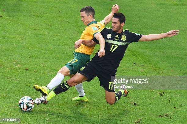 Koke of Spain challenges Matt McKay of Australia during the 2014 FIFA World Cup Brazil Group B match between Australia and Spain at Arena da Baixada...