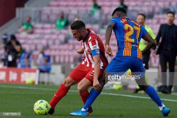 Koke Resurreccion of Atletico Madrid and Ilaix Moriba Kourouma of Barcelona compete for the ball during the La Liga Santander match between FC...