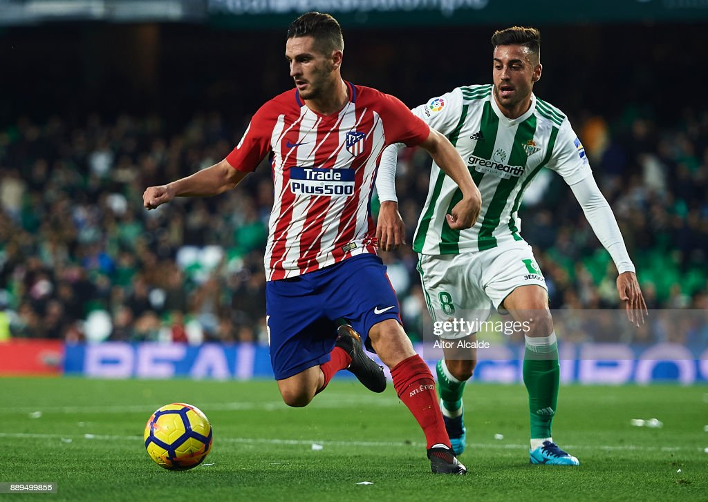 Koke Resurreccion of Club Atletico de Madrid (L) being followed by Victor Camarasa of Real Betis Balompie (R) during the La Liga match between Real Betis and Atletico Madrid at Estadio Benito Villamarin on December 10, 2017 in Seville, .