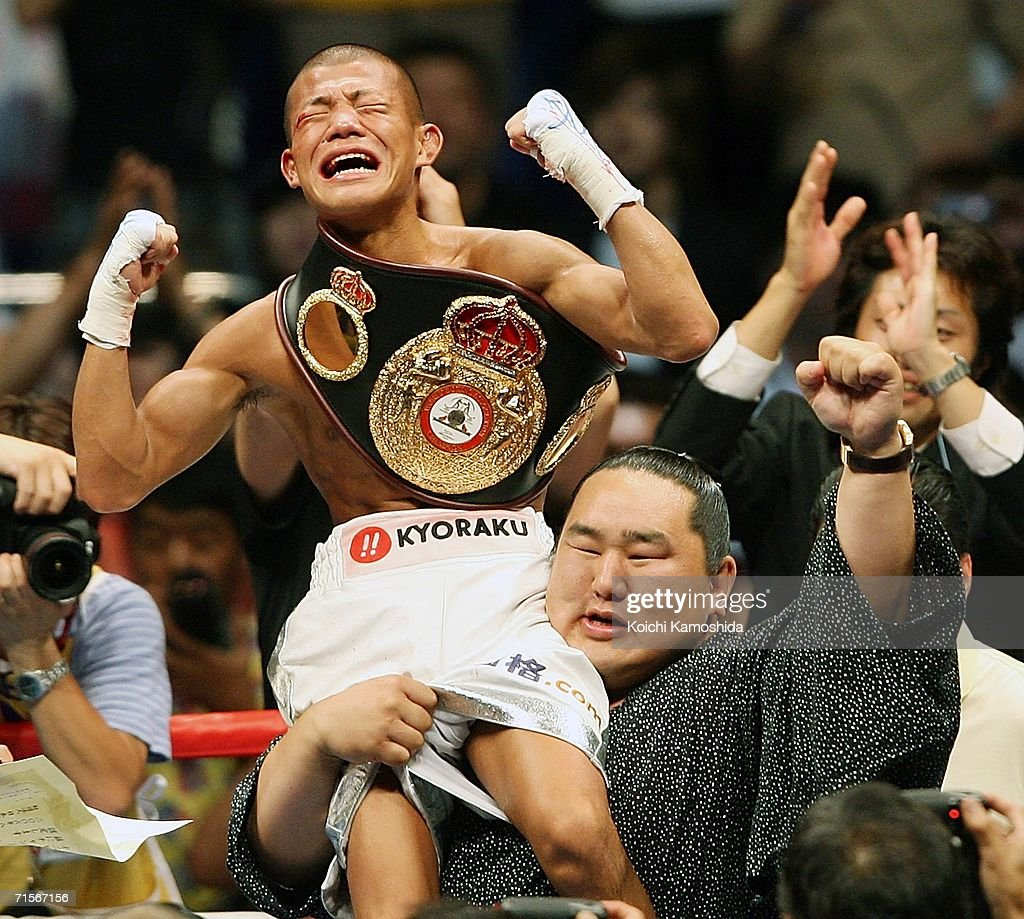 Koki Kameda of Japan is lifted by a Mongolian sumo grand champion Asashoryu after defeating Juan Jose Landaeta of Venezuela to win the World Boxing Association light flyweight title bout at Yokohama Arena August 2, 2006 in Yokohama, Japan.