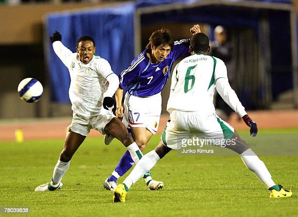Koki Mizuno of Japan battles for the ball against Abdulmalek Abdullah Al Khaibri and Jufain Ali Al Bishi of Saudi Arabia during 2008 Beijing Olympic...