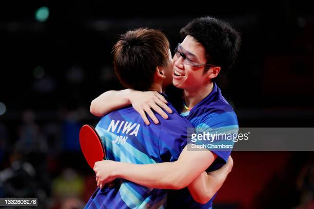 Koki Niwa and Mizutani Jun of Team Japan hug during their Men's Team Bronze Medal table tennis match on day fourteen of the Tokyo 2020 Olympic Games...