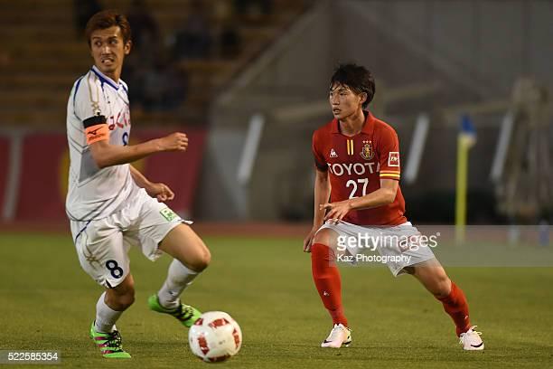 Koki Sugimori of Nagoya Grampus sends the pass while Ryohei Arai watches during the J.League Yamazaki Nabisco Cup match between Nagoya Grampus and...