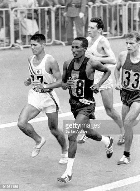Kokichi Tsuburaya of Japan compete with Abebe Bikila of Ethiopia in the men's marathon during the Tokyo Olympic on October 21 1964 in Tokyo Japan