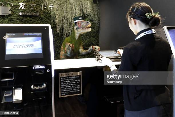 A Kokoro Company Ltd robotic dinosaur stands at the reception desk of the Henn na Hotel Maihama Tokyo Bay operated by HIS Hotel Holdings Co a unit of...