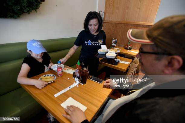 Kokoro waitress Lenny Sentiono has work there for 25 years serves Alex Roldan and Addison Roldan 6yearsold on December 29 2017 in Denver Colorado The...