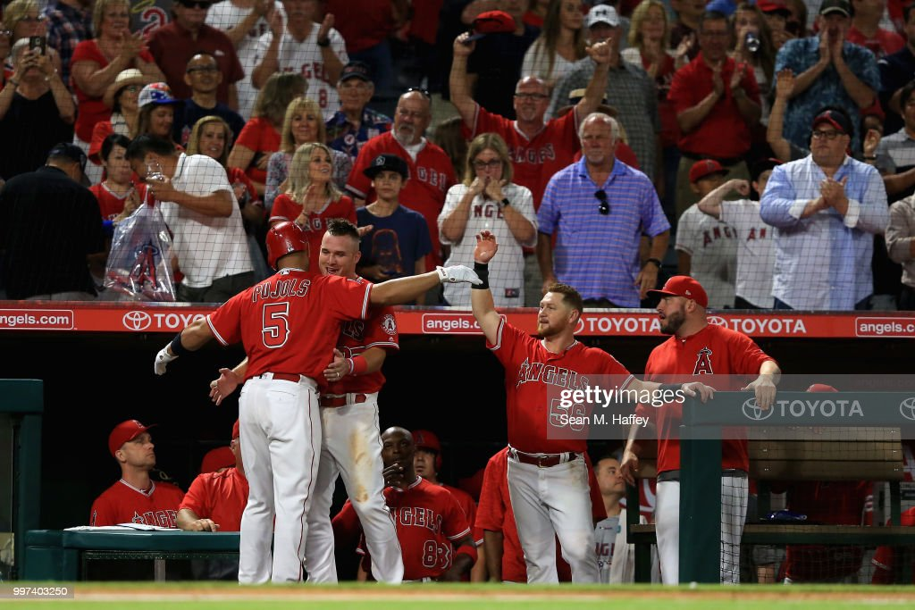 Kole Calhoun #56 and Mike Trout #27 congratulate Albert Pujols #5 of the Los Angeles Angels of Anaheim at the dugout after his solo homerun during the sixth inning of a game against the Seattle Mariners at Angel Stadium on July 12, 2018 in Anaheim, California.