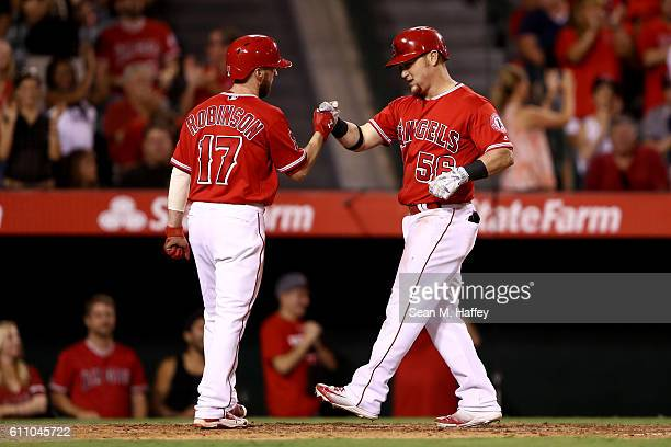 Kole Calhoun is congratulated by Shane Robinson of the Los Angeles Angels of Anaheim after hitting a tworun homerun during the fourth inning of a...