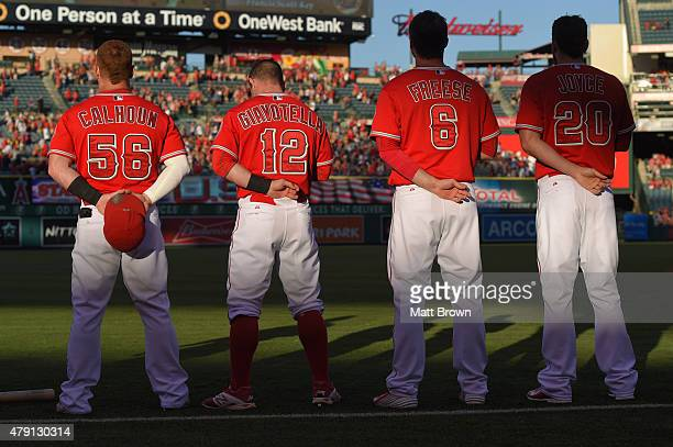 Kole Calhoun Johnny Giavotella David Freese and Matt Joyce of the Los Angeles Angels of Anaheim listen to the national anthem before the game against...