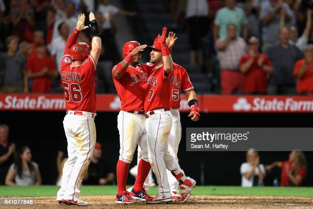 Kole Calhoun Luis Valbuena and Albert Pujols congratulate Cliff Pennington of the Los Angeles Angels at homeplate after he hit a grandslam homerun...