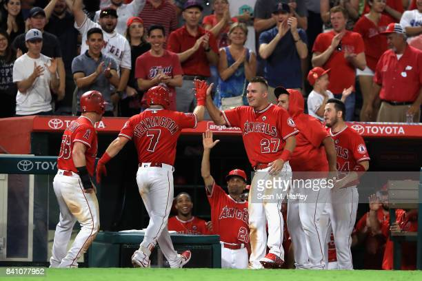 Kole Calhoun Mike Trout and CJ Cron congratulate Cliff Pennington of the Los Angeles Angels after his grandslam homerun during the seventh inning of...