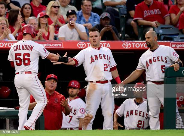 Kole Calhoun of the Los Angeles Angels celebrates his run with Mike Trout and Albert Pujols to trail 31 to the Oakland Athletics during the second...