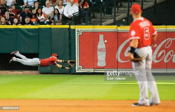 Kole Calhoun of the Los Angeles Angels dives for a ball in right field as Albert Pujols looks on from first base in the first inning of their game...