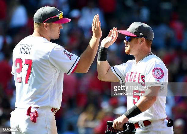 Kole Calhoun of the Los Angeles Angels gets a high five from Mike Trout of the Los Angeles Angels after the game against the Detroit Tigers at Angel...