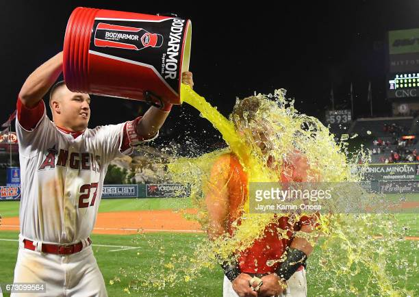 Kole Calhoun of the Los Angeles Angels gets douced with a cooler of Bodyarmor sports drink by Mike Trout of the Los Angeles Angels after he singled...