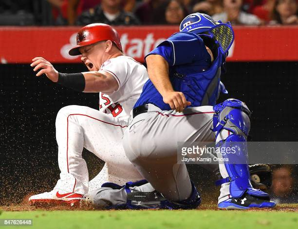 Kole Calhoun of the Los Angeles Angels of Anaheim beats the throw to Brett Nicholas of the Texas Rangers to score a run on a single by Andrelton...