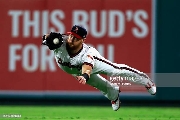 Kole Calhoun of the Los Angeles Angels of Anaheim dives to catch a line drive hit by Nolan Arenado of the Colorado Rockies during the fourth inning...